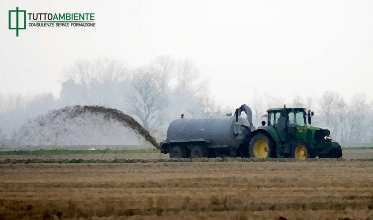 Un trattore concima un campo agricolo spargendo fanghi e liquami