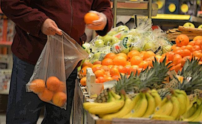 Un consumatore al supermercato infila arance in un sacchetto di plastica