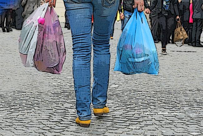 Una donna trasporta sacchetti di plastica per la spesa